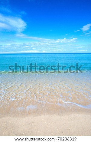 Beautiful beach with crystal clear blue waters of the Andaman sea against blue sky inThailand.