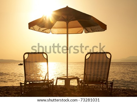 Beautiful  beach with deck chairs and parasol at sunset - stock photo