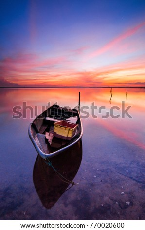 Beautiful beach with fisherman boat during sunrise at Jubakar beach Kelantan, Malaysia. Soft focus due to long exposure.