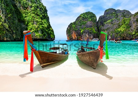 Beautiful beach with thai traditional wooden longtail boat and blue sky in Maya bay, Thailand. Vacation holidays summer background. View of nice tropical beach in Maya bay near Phuket in Thailand.