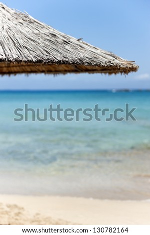 Beautiful beach with turquoise clear water and a close up of a bamboo parasol