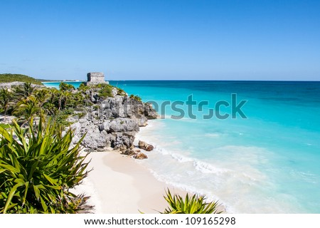 Beautiful beach with turquoise water  in Tulum Mexico, Mayan ruins on top of the cliff.