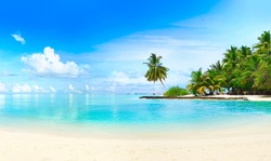 Beautiful beach with white sand, turquoise ocean, green palm trees and blue sky with clouds on Sunny day. Summer tropical landscape, panoramic view.