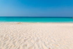 Beautiful beach with white sand, turquoise ocean water and blue sky. Natural background for summer vacation, soft focus.