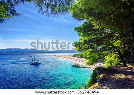 Beautiful beach Zlatni Rat or Golden Cape on island Brac in Croatia with yacht