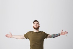 Beautiful bearded european man with tatooed arm and dark hair in casual olive t-shirt spreading hands widely, looking upside, being sutisfied and carefree. Guy feeling free after month of hard work.