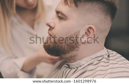 beautiful bearded man cutting the hair and beards in the barbershop