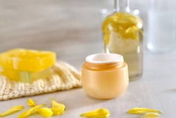 Beautiful beauty composition of cosmetic products.   Opened Jar with face cream with calendula,  extract. petals of calendula, chrysanthemum. Selective focus