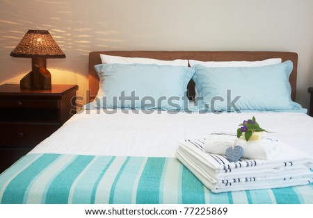 Beautiful bedroom interior with white sheets and striped towels