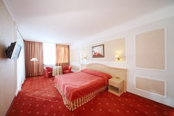 Beautiful bedroom with double bed with red linen, red armchairs and window.