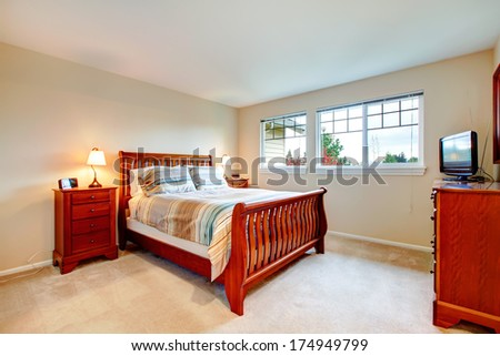 Beautiful bedroom with  light tones wall and carpet floor naturally matching brown wood bedroom furniture.