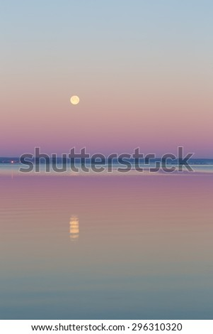 Beautiful before sunrise landscape of Gdanska Bay with setting moon photographed in Poland. Baltic sea shore.