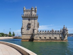 Beautiful Belém Tower or Saint Vincent Torre de Belém. Ancient, historic fortified quarter of Portuguese Manueline style on the northern bank of the Tagus river in Lisbon, in the blue sky background.