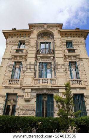 Beautiful Belle Epoque ornate stone building with balcony and traditional green shutter windows on blue sky background,Nice,Cote d\'Azur, France.