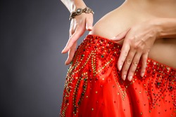 Beautiful belly dancer young woman in gorgeous red and green costume dress. Part of body
