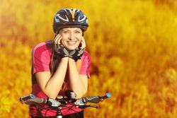 beautiful bicyclist woman on sunset yellow field background