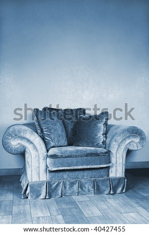 Beautiful big armchair with soft pillows in an apartment