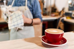 Beautiful big red cup of coffee stands on light coloured wooden table, heart cappuccino art, background of barista with towel, close up