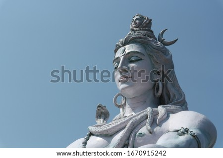 Beautiful big statue of meditating Shiva. Lord Shiva sits near the Ganges River at the foot of the Himalayas in Rishikesh, India. Yoga and meditation concept.