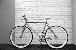 Beautiful bike leaning against brick wall in black and white style