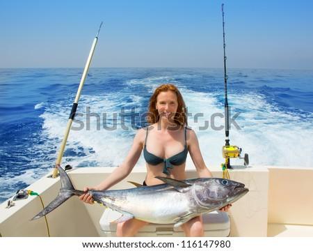 beautiful bikini fisher woman holding big bluefin tuna catch on boat deck