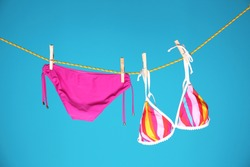 Beautiful bikini hanging on rope against color background