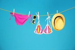 Beautiful bikini, hat and sunglasses hanging on rope against color background