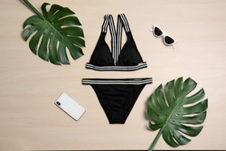Beautiful bikini, mobile phone and sunglasses on wooden background, top view