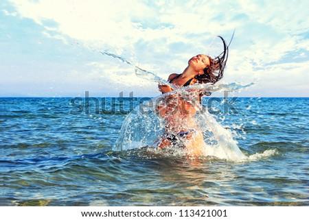 Beautiful bikini model splashing water