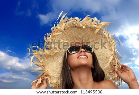Beautiful bikini model with straw hat and sunglasses posing on the beach