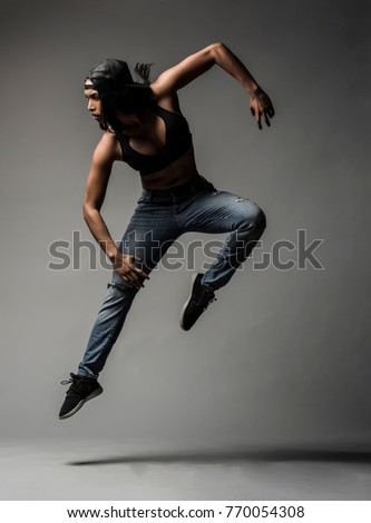 Beautiful Biracial Asian Black Dancer wearing blue jeans and baseball cap does a creative urban dance move against a grey backdrop in studio with dramatic lighting #770054308