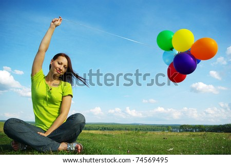 Beautiful birthday girl sitting with colorful baloons