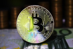 Beautiful Bitcoin BTC on the background of euro banknote and gold coins.