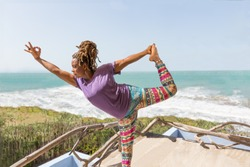 Beautiful Black, African, or Carribean woman practicing wellness and yoga poses at resort or hotel outdoors overlooking gorgeous beach and ocean.