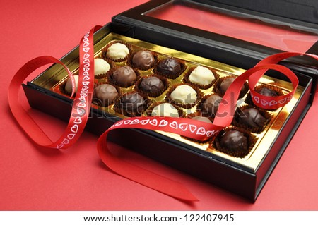 Beautiful black and gold closed box of delicious chocolates in a black and gold box with red heart ribbon on a red background, for Valentine, Christmas, birthday or Mothers Day gift.
