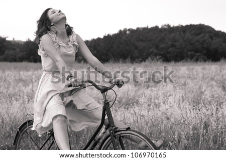 Beautiful black and white image of young woman riding bike in a country road.