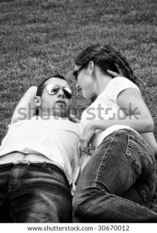 beautiful black and white of young punk lovers laying on the grass wearing sunglasses and talking