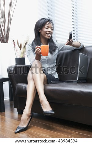 beautiful black businesswomen on the phone at home laughing
