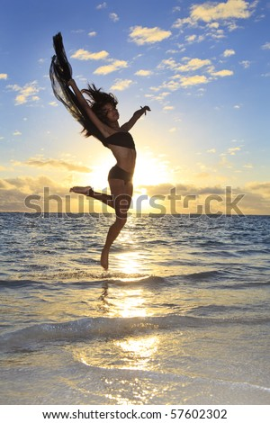 beautiful black female dancer leaping in the air over the ocean at sunrise in the tropics