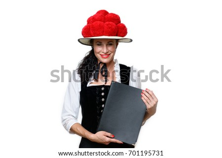 Beautiful Black forest waitress wearing a Bollenhut, the traditional hat with fourteen red pompoms, standing smiling at the camera holding a menu isolated on white #701195731