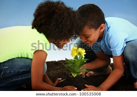 Beautiful Black Girl and Boy Child, Brother and Sister, in the Soil, Planting Flowers for Earth Day