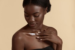 Beautiful black girl apply cosmetic cream on body. Serious young woman with perfect skin. Concept of skincare. Isolated on beige background. Studio shoot