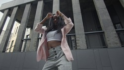 Beautiful Black Girl Dancing On The Street. Behind Her Tall Buildings. Beautiful Stylish Girl With Long Hair On Business Clothes Dances Modern Dances. She Makes Rhythmic Movements With Her Body.