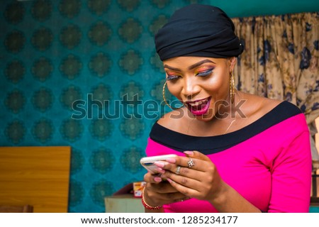 beautiful black girl excited and happy while looking at her phone #1285234177