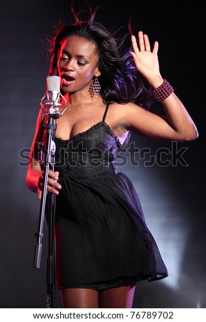Beautiful black girl on stage with microphone singing, wearing a black dress and purple bead bracelet.