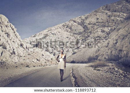 Beautiful black girl, with a white dress, walking on a long road of mountains