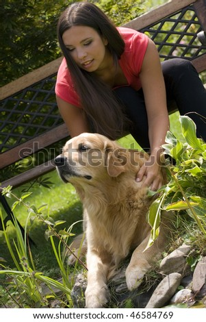 Beautiful black hair woman and golden retriever in the garden