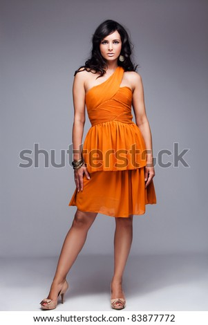 beautiful black hair woman in elegant orange dress, studio shot, full body shot