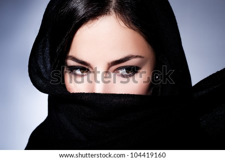 beautiful black hair woman with black scarf over her face, studio closeup