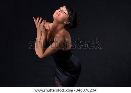 Beautiful black hairs women wearing evening dress on black background #346370234
